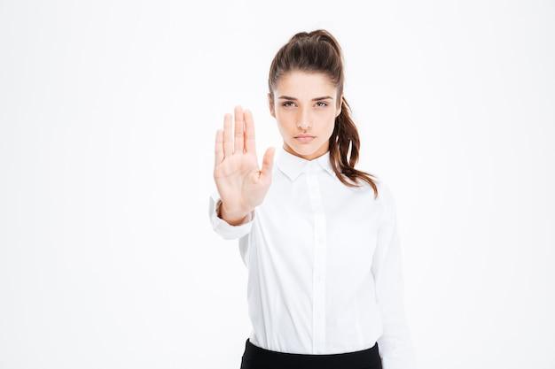 Jolie jeune femme d'affaires confiante debout et montrant un geste d'arrêt