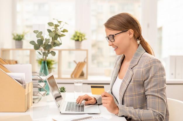Jolie jeune femme d'affaires élégante avec carte en plastique assis devant un ordinateur portable lors de la recherche de marchandises dans la boutique en ligne
