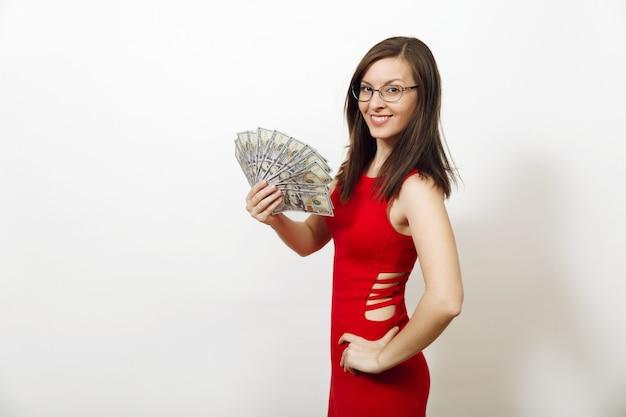 Jolie jeune femme d'affaires heureuse caucasienne en robe rouge ajustée et lunettes tenant des billets d'argent sur fond blanc. belle fille avec caméra à la recherche d'argent isolé.