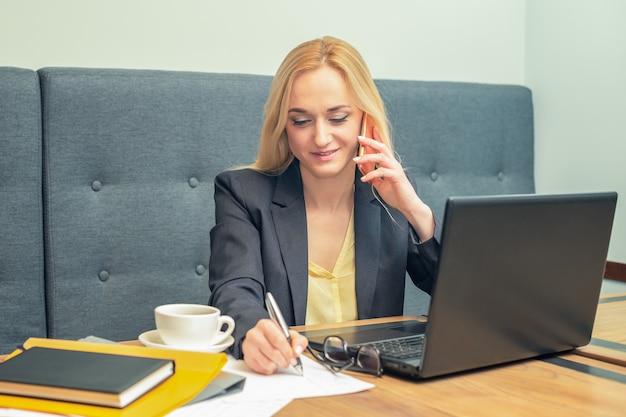 Jolie jeune femme d'affaires parle au téléphone tout en écrivant sur un papier au bureau
