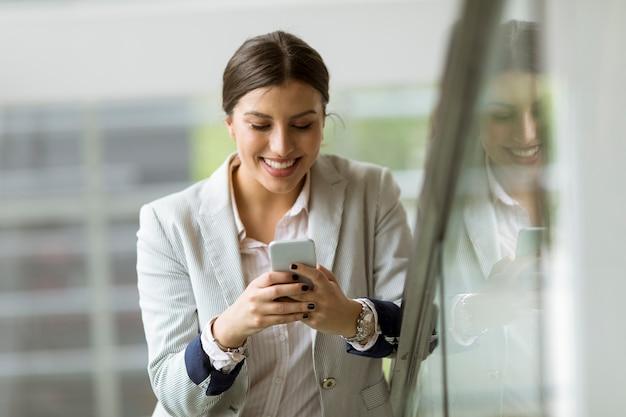 Jolie jeune femme d'affaires se dresse sur les escaliers au bureau et utilise un téléphone mobile
