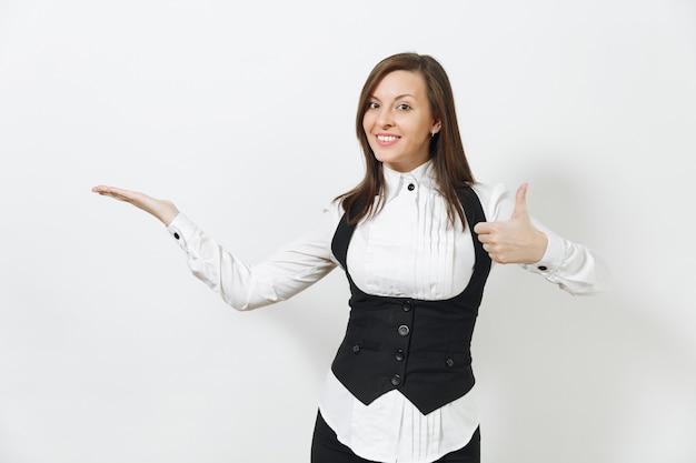 Jolie jeune femme d'affaires souriante aux cheveux bruns en costume noir, chemise blanche, pointant la main de côté, montrant le pouce vers le haut isolé sur mur blanc