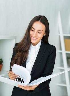 Jolie jeune femme d'affaires tournant les pages du document dans le dossier