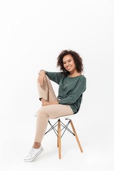 Jolie jeune femme africaine assise sur une chaise isolée sur un mur blanc, posant