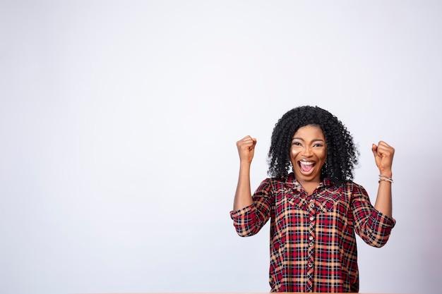 Une jolie jeune femme africaine excitée assise à un bureau, heureuse et fait des gestes vers l'espace de son côté