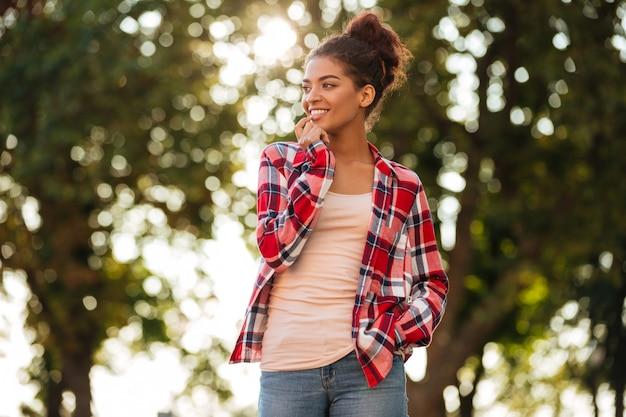 Jolie jeune femme africaine marchant à l'extérieur dans le parc.