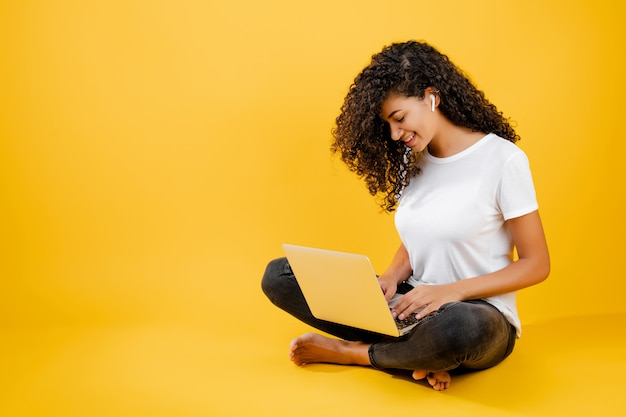 Jolie jeune femme africaine noire assise avec ordinateur portable et écouteurs isolés sur jaune