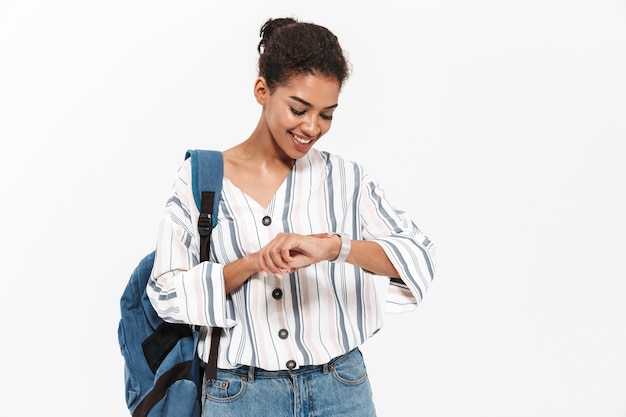 Jolie jeune femme africaine portant des vêtements décontractés, debout isolée sur un mur blanc, portant un sac à dos, vérifiant l'heure