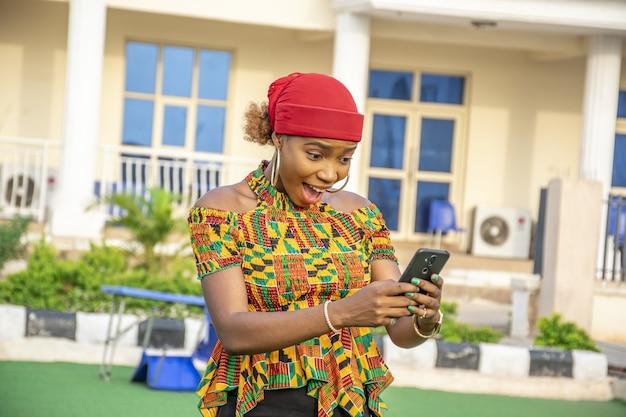 Jolie jeune femme africaine tenant son téléphone, se sentant excitée