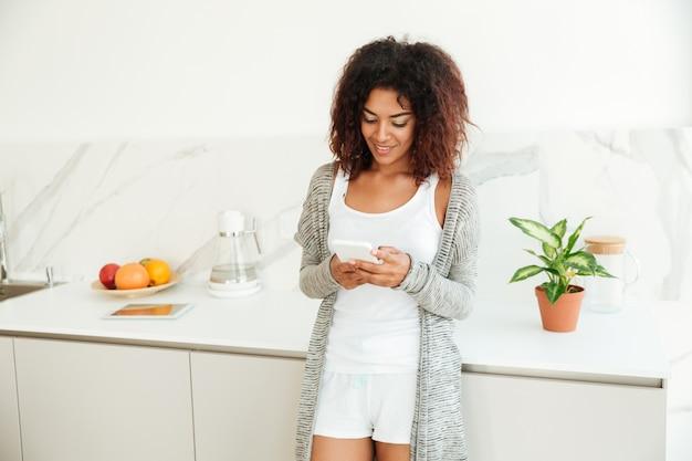 Jolie jeune femme afro-américaine à l'aide de téléphone portable