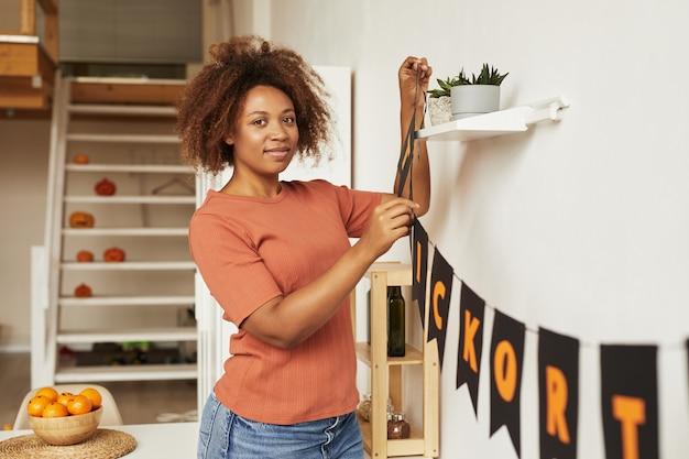 Jolie jeune femme afro-américaine décoration chambre avec guirlande pour la fête d'halloween, espace copie