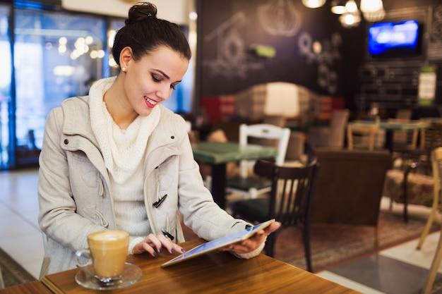 Jolie jeune femme à l'aide d'une tablette numérique au café