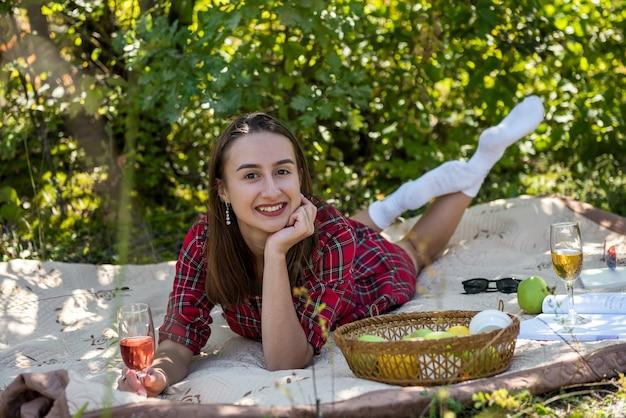 Jolie jeune femme allongée dans le parc, souriante et profitant d'une journée ensoleillée d'été