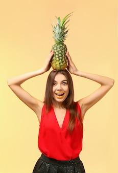 Jolie jeune femme à l'ananas sur la couleur