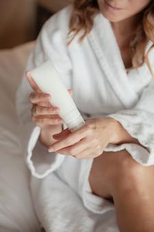 Jolie jeune femme appliquant la crème à la main