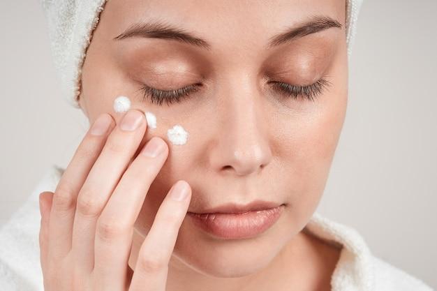 Jolie jeune femme applique la crème sur la peau sous les yeux