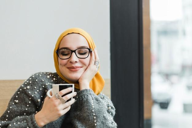 Jolie jeune femme appréciant un café