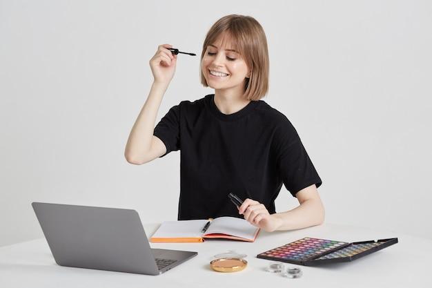 Une jolie jeune femme apprend l'art du maquillage à distance, en utilisant un ordinateur portable et un appel vidéo, sur internet, en restant à la maison.