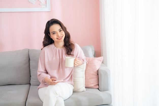 Jolie jeune femme asiatique à l'aide de téléphone et de boire du café assis sur un canapé à la maison.