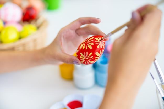 Jolie jeune femme asiatique aime peindre une aquarelle sur des œufs fantastiques pour le festival des œufs de pâques.