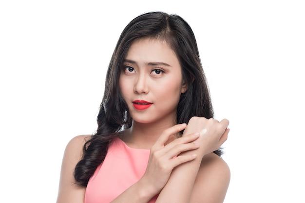 Jolie jeune femme asiatique appliquant de la crème sur sa main