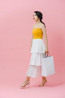 Jolie jeune femme asiatique glamour posant avec des sacs blancs d'achats