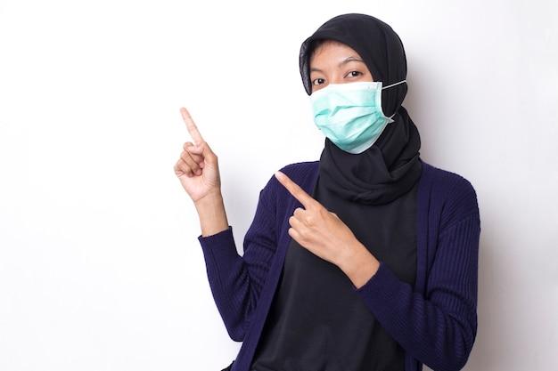 Jolie jeune femme asiatique musulmane avec masque de protection médicale pour protéger l'infection par le coronavirus sur un espace blanc isolé