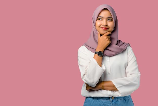 Jolie jeune femme asiatique pensant avec visage souriant sur fond rose