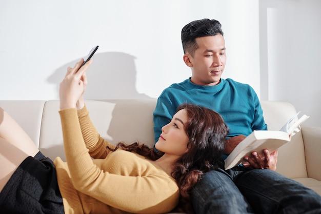 Jolie jeune femme asiatique prenant selfie en se reposant la tête sur les genoux du livre de lecture de petit ami