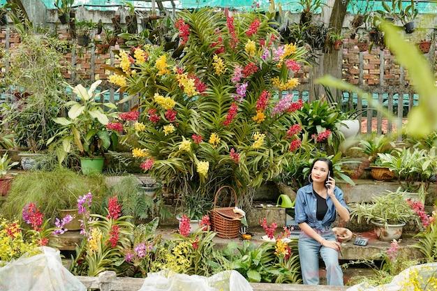 Jolie jeune femme asiatique travaillant en serre avec de nombreuses fleurs épanouies autour, elle parle au téléphone avec le client