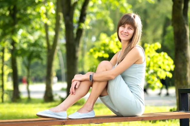 Jolie jeune femme assise sur un banc dans le parc d'été.