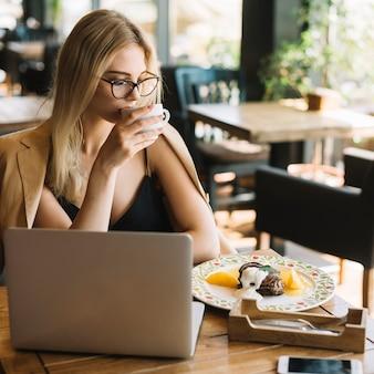 Jolie jeune femme assise à café buvant du café