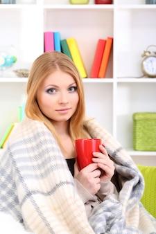 Jolie jeune femme assise sur un canapé, tenant une tasse avec une boisson chaude, sur fond intérieur de maison