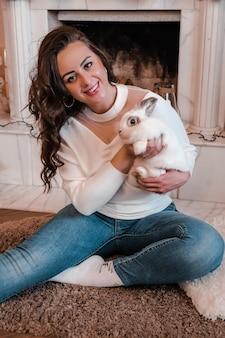 Jolie jeune femme assise à côté de la cheminée et tenant un lapin. animaux et personnes. home sweet home, hygge. animaux à la maison. lapin domestique.