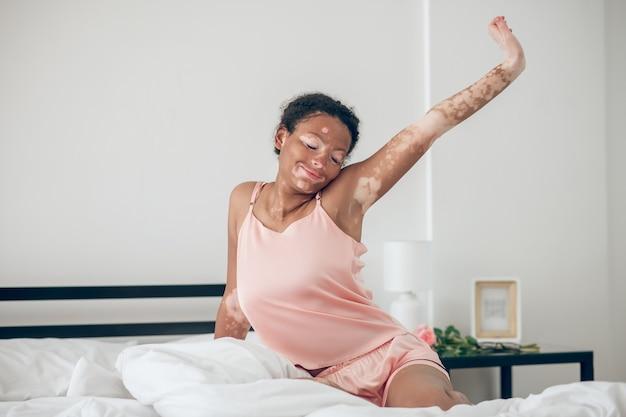 Une jolie jeune femme assise sur le lit en lingerie rose et s'étirant