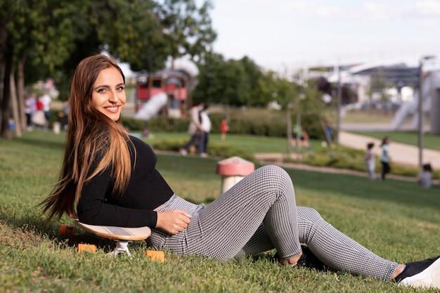 Jolie jeune femme assise sur sa planche à roulettes dans le parc