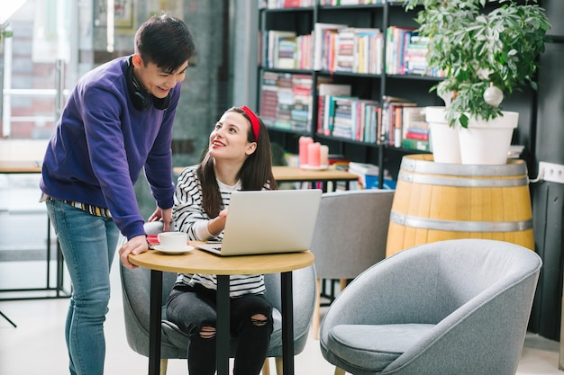 Jolie jeune femme assise à la table dans une bibliothèque et regardant le jeune homme tout en pointant vers l'écran d'un ordinateur portable