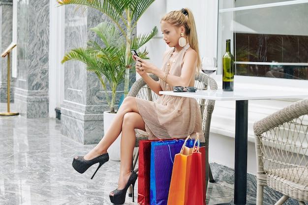Jolie jeune femme assise à table dans un café en plein air après le shopping, boire du vin et envoyer des sms à des amis