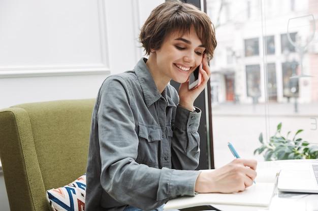 Jolie jeune femme assise à la table du café à l'intérieur, travaillant avec de la paperasse, parlant au téléphone mobile