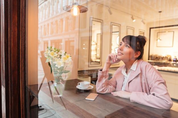 Jolie jeune femme assise à la table du café
