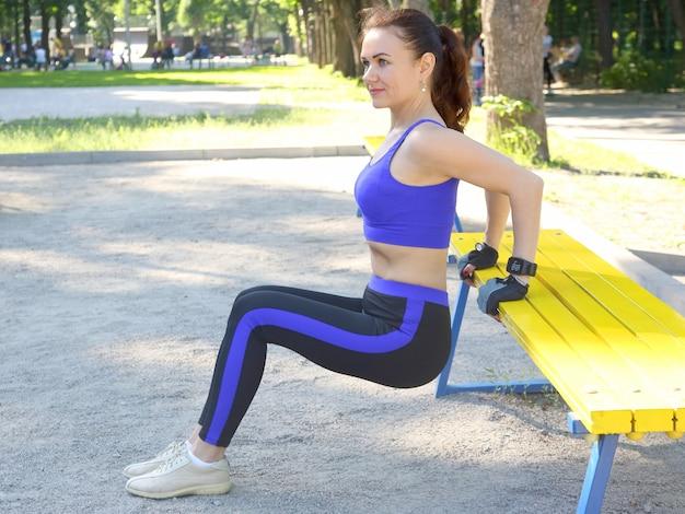 Jolie jeune femme athlétique faisant de la gymnastique sur ses mains