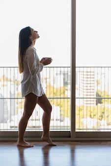 Une jolie jeune femme au balcon tenant une tasse de café du matin