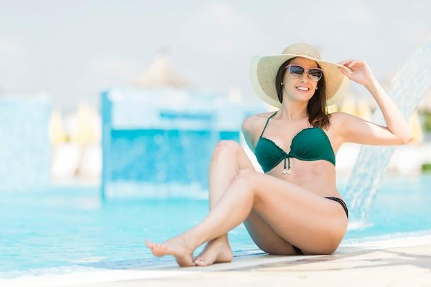 Jolie jeune femme au bord de la piscine