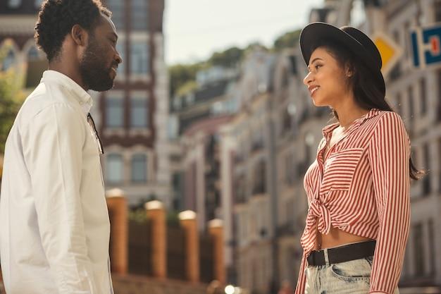 Jolie jeune femme au chapeau debout dans la rue devant son ami et le regardant