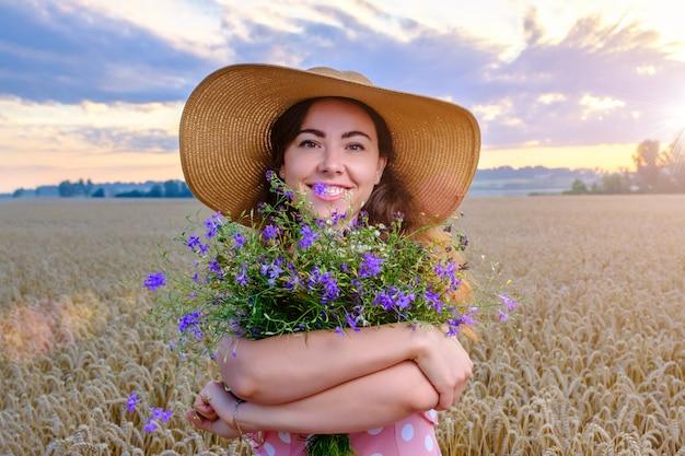 Jolie jeune femme au chapeau de paille tient un bouquet de fleurs sauvages dans un champ de blé au lever du soleil