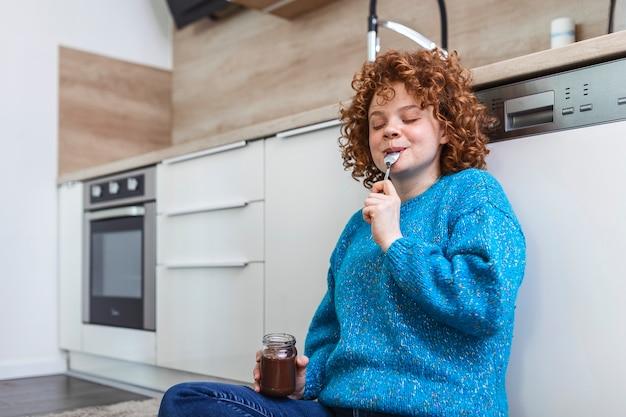 Jolie jeune femme au gingembre dans des vêtements modernes et élégants bénéficiant de délicieux chocolat à tartiner avec un sourire mignon dans la cuisine interier.