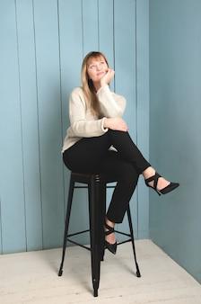 Jolie jeune femme aux cheveux blonds qui coule juste en dessous de ses épaules, assise sur une chaise haute lève les yeux rêveusement, posant sa tête sur sa main sur le mur de planches de bois bleues.