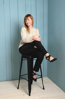 Jolie jeune femme aux cheveux blonds qui coule juste en dessous de ses épaules, assise sur les jambes de la chaise haute croisées sur le mur de planches de bois bleues.