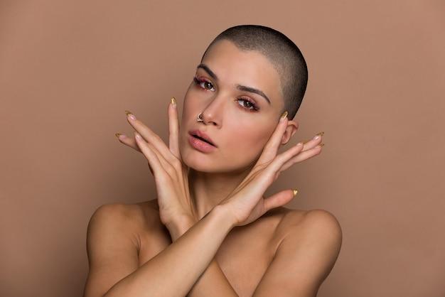 Jolie jeune femme aux cheveux courts posant sur beige