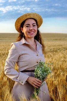 Jolie jeune femme aux cheveux longs en chapeau de paille souriant et tient un bouquet de fleurs sauvages dans un champ de blé au lever du soleil.